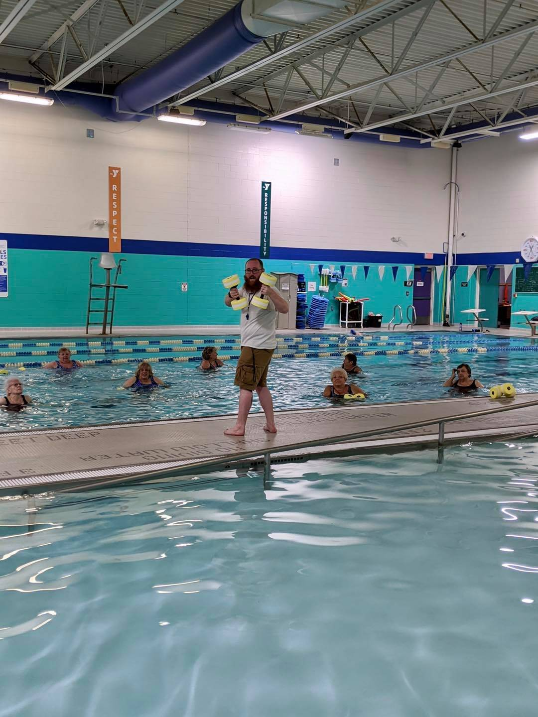 Adults in a pool with instructor on the deck
