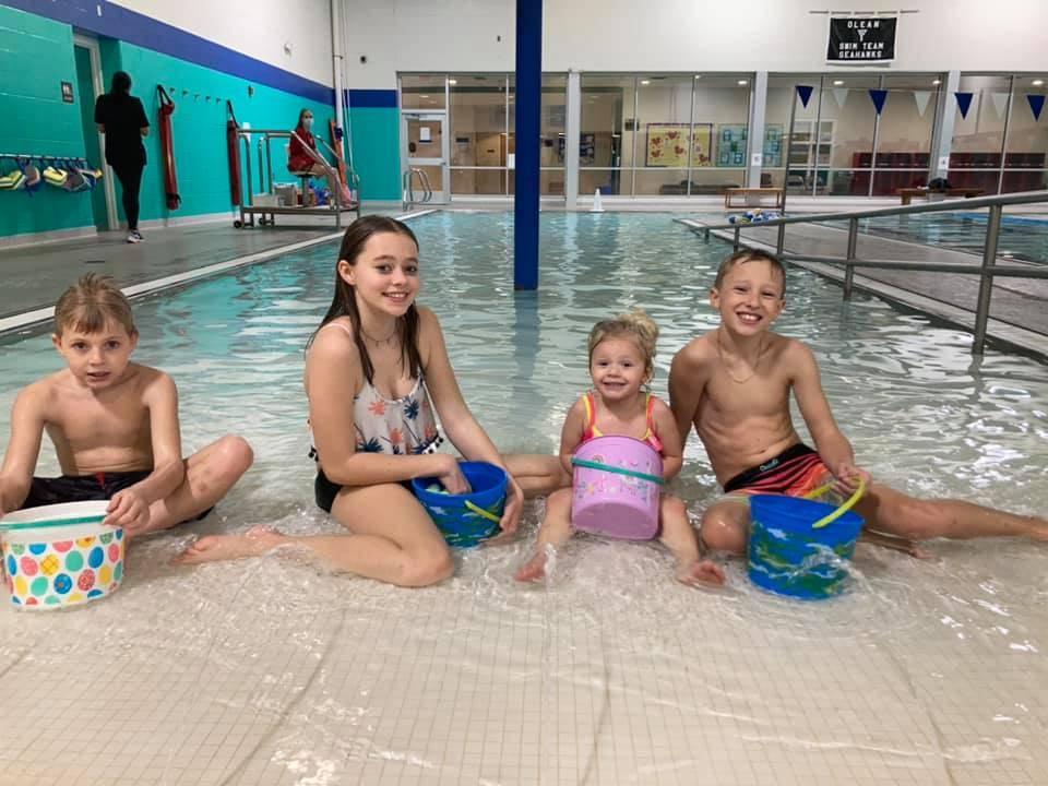 Four children sitting near the swimming pool