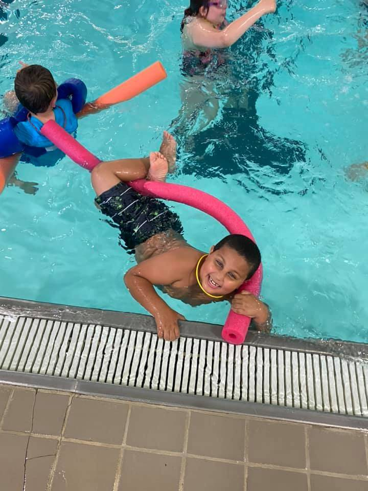 Boy in swimming pool with pool noodle