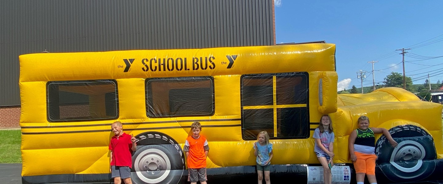 five young kids in front of an inflatable school bus