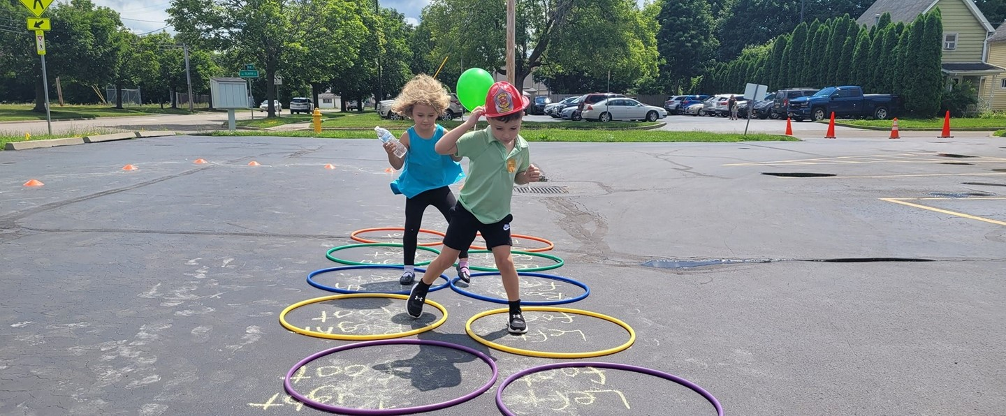 two young kids jumping in hula hoops on a parking lot