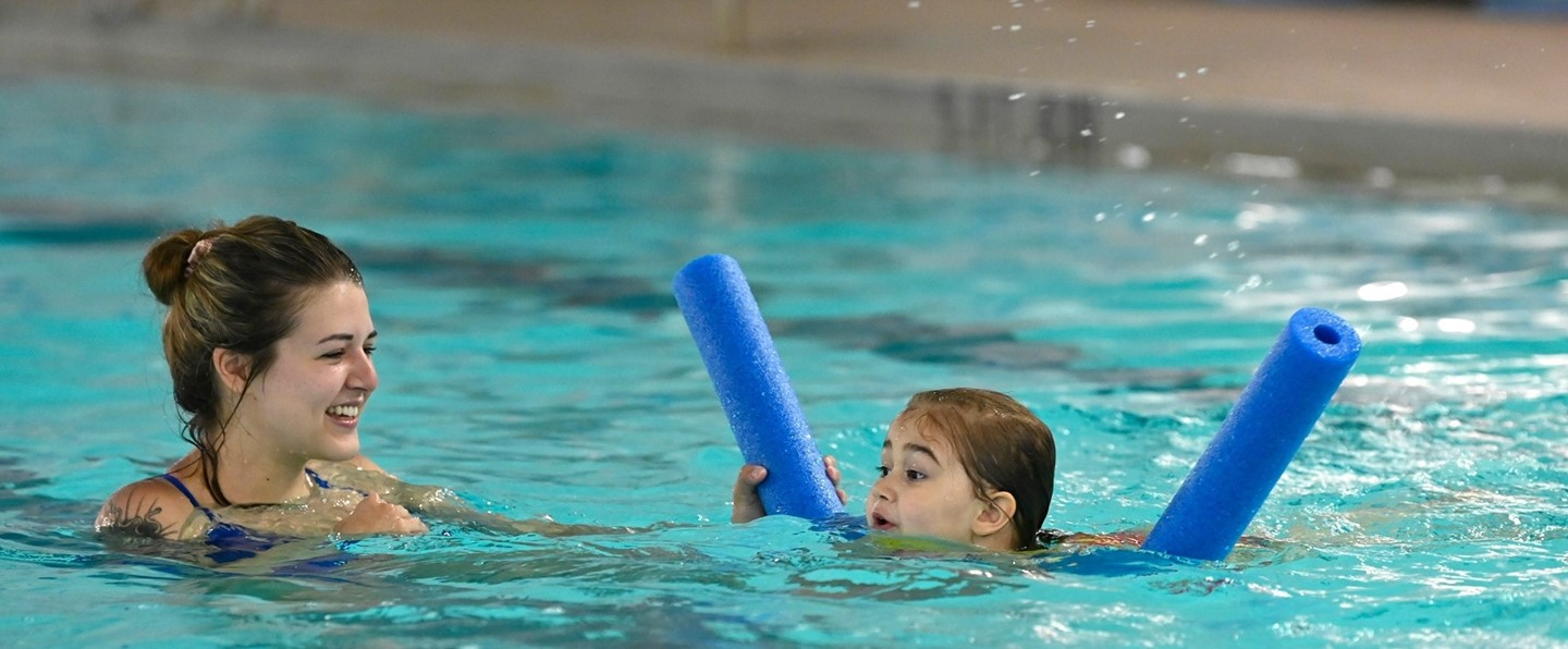young girl and female instructor doing a swim lesson in the pool