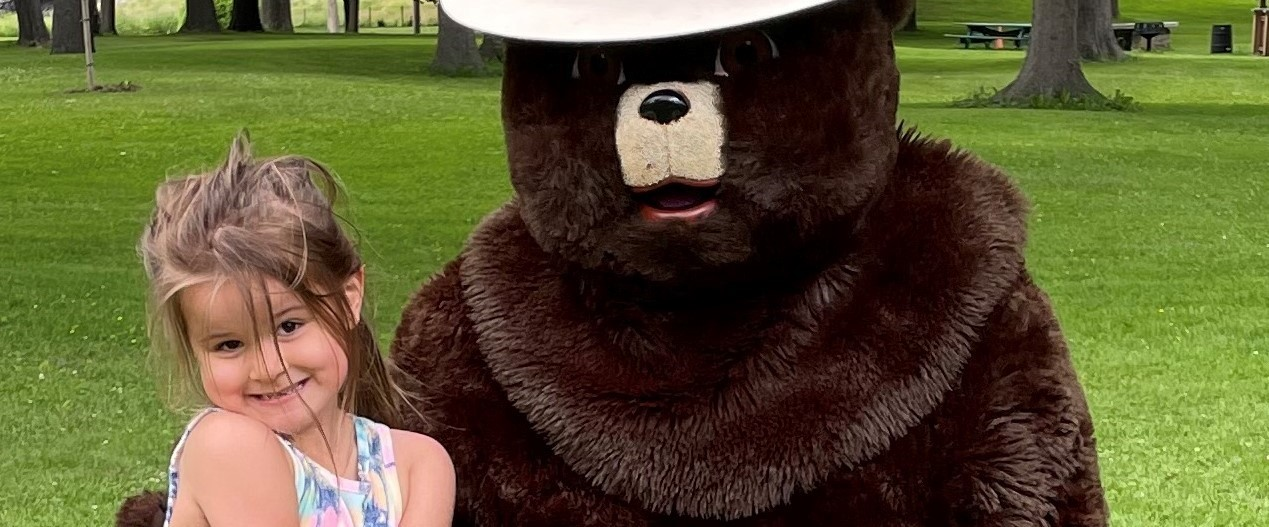 young girl with Smokey the Bear