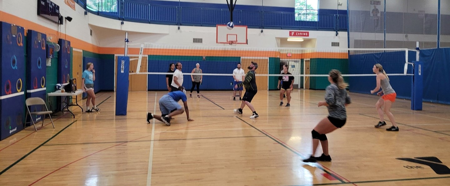 adults playing indoor volleyball