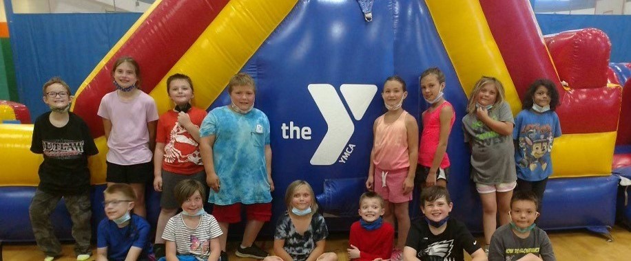 children in front of an inflatable slide