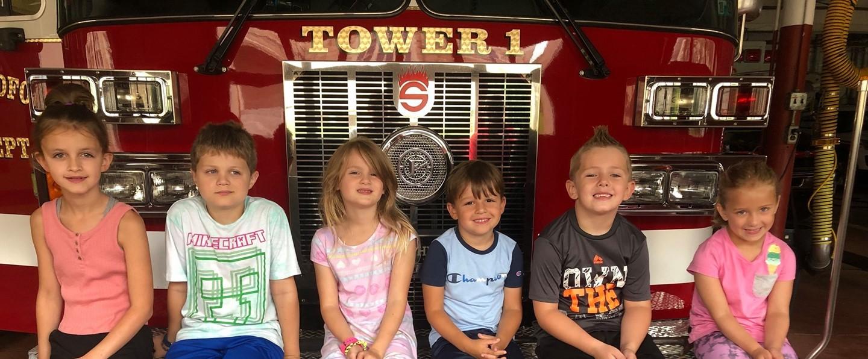 children sitting on a fire truck