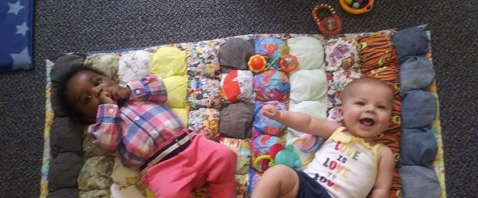 two babies on a blanket