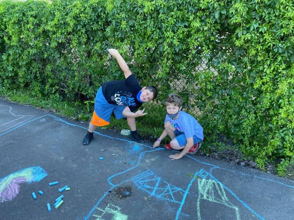 young boys playing with sidewalk chalk