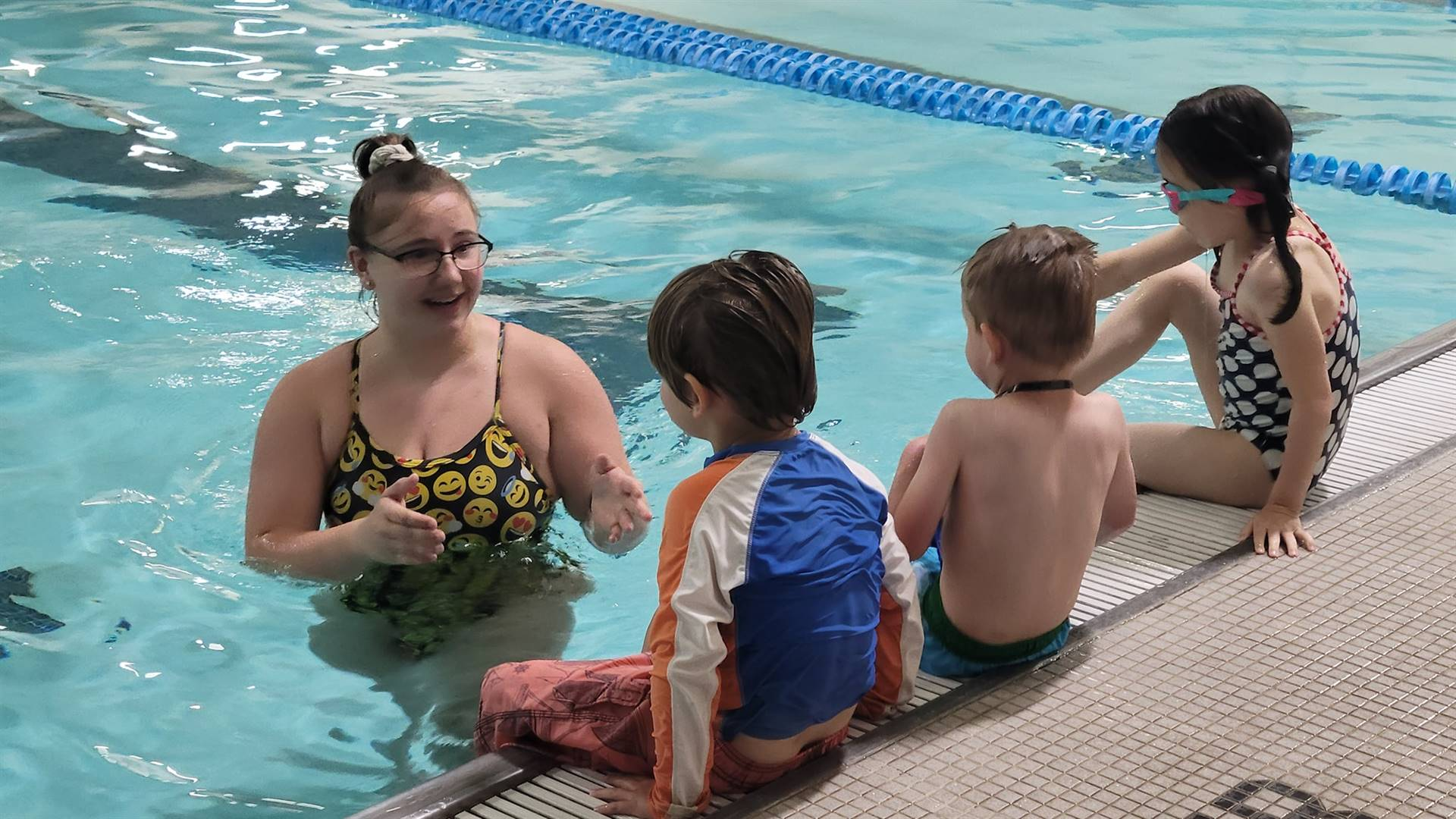 Three children sitting on edge of pool with instructor in the water