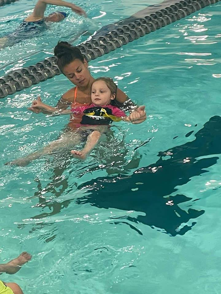 Toddler girl learning to swim in pool with instructor
