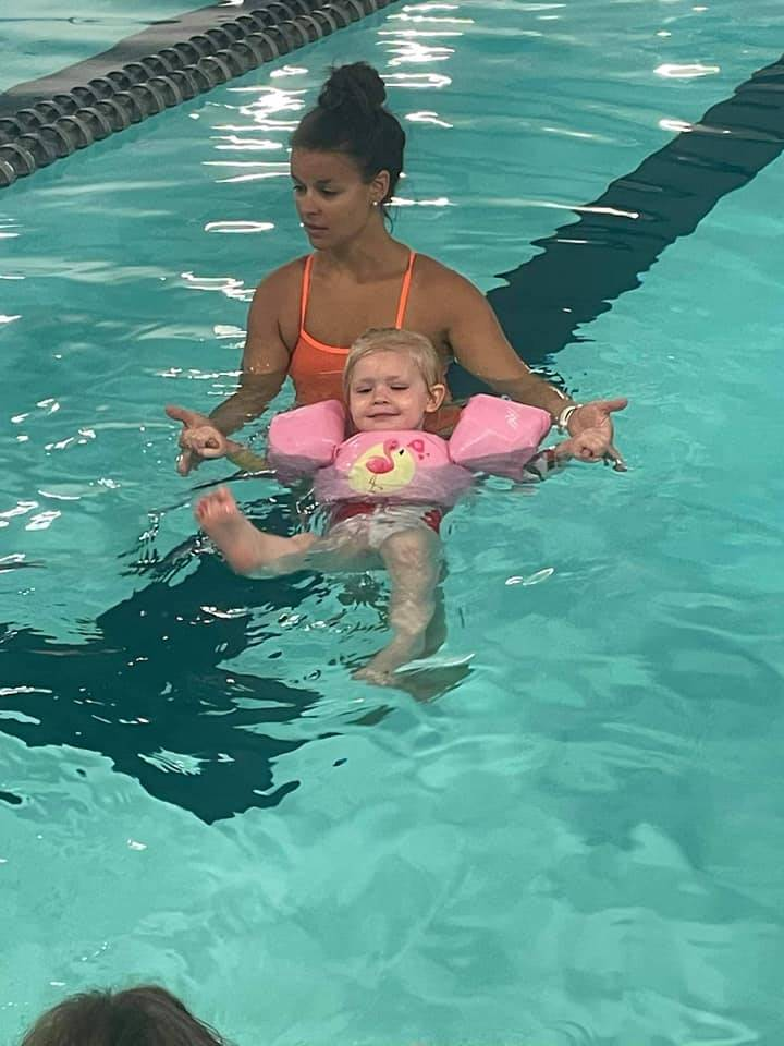 Toddler learning to swim in a pool with instructor