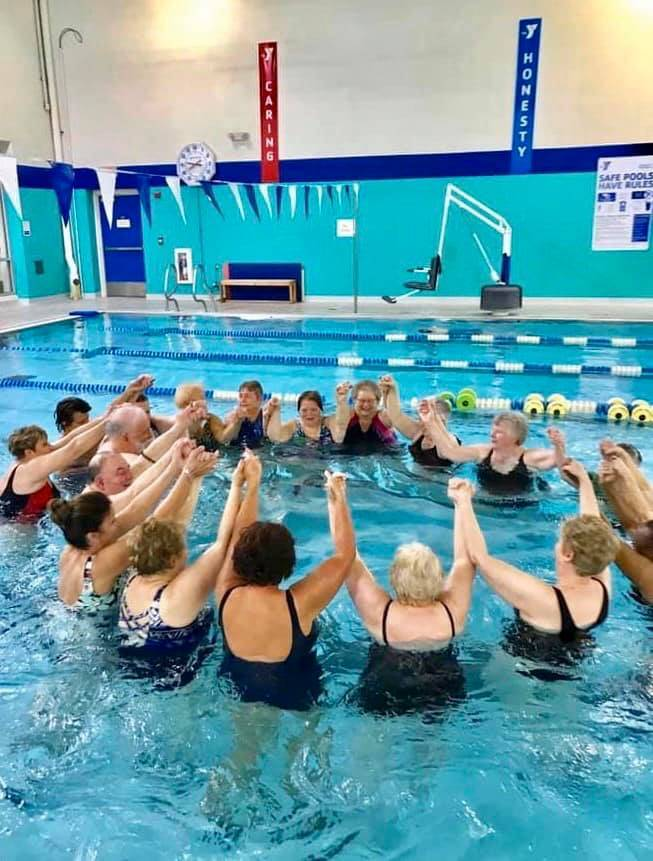 Active older adults hold hands in a pool as a group