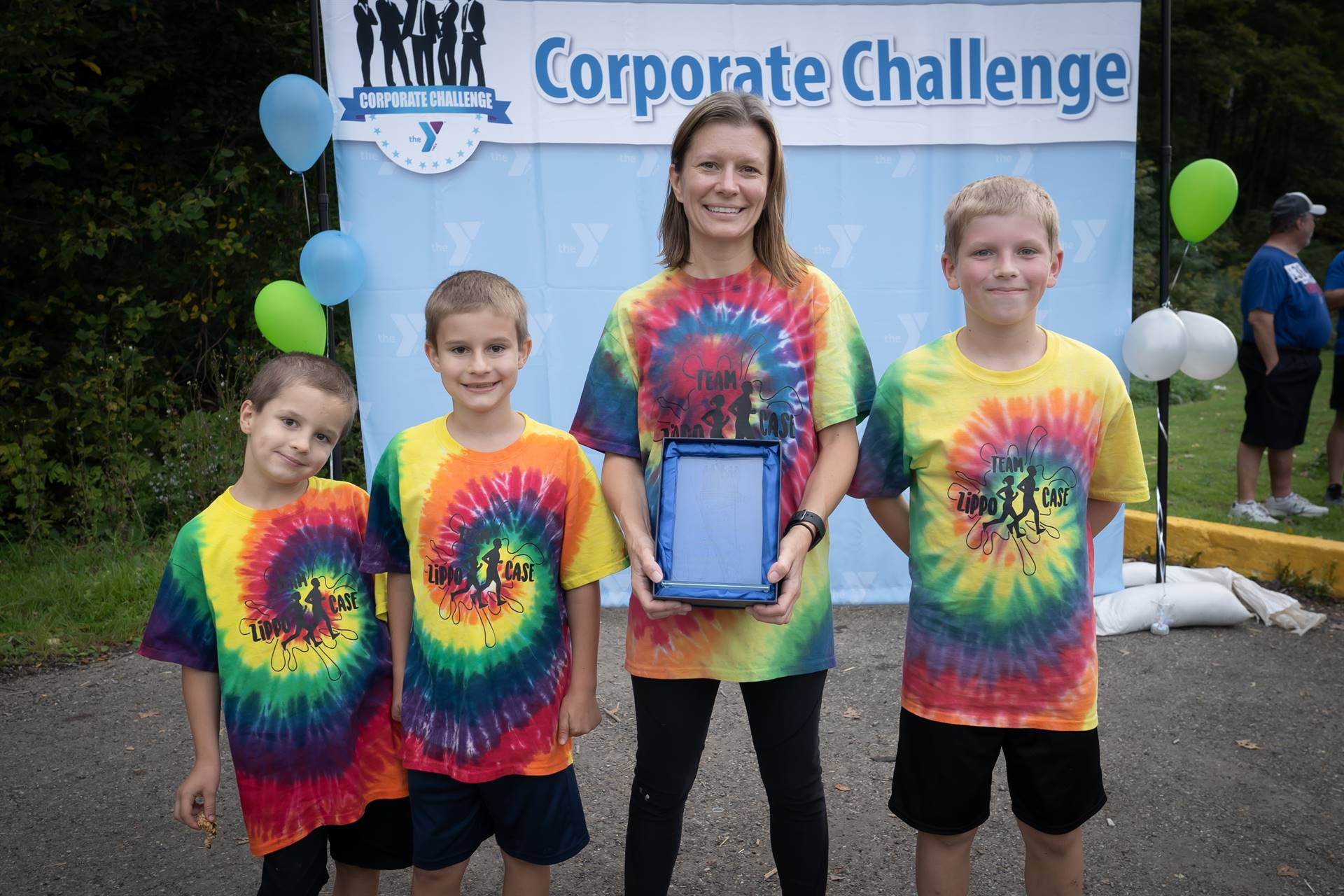 Woman and three kids in front of corporate challenge banner
