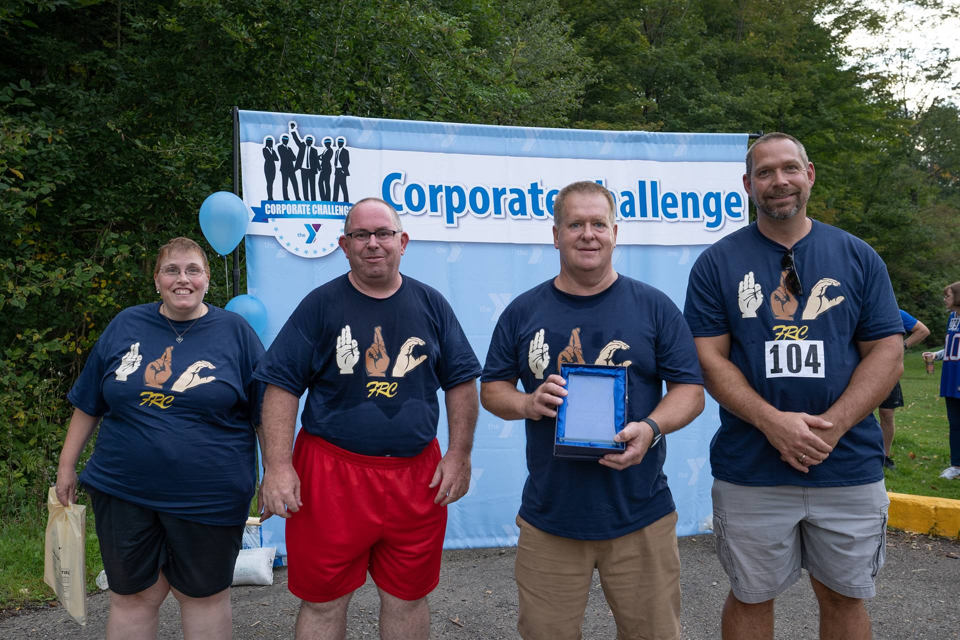Four employees in front of corporate challenge banner