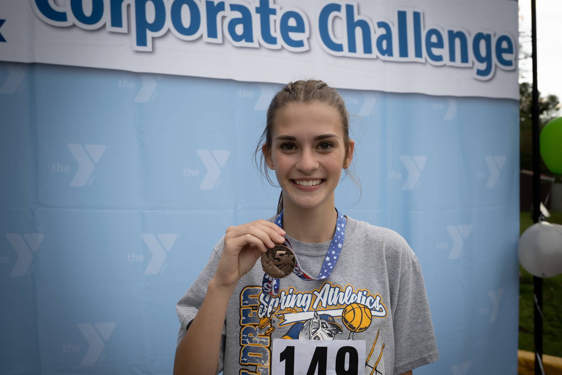 woman holding up 5k medal