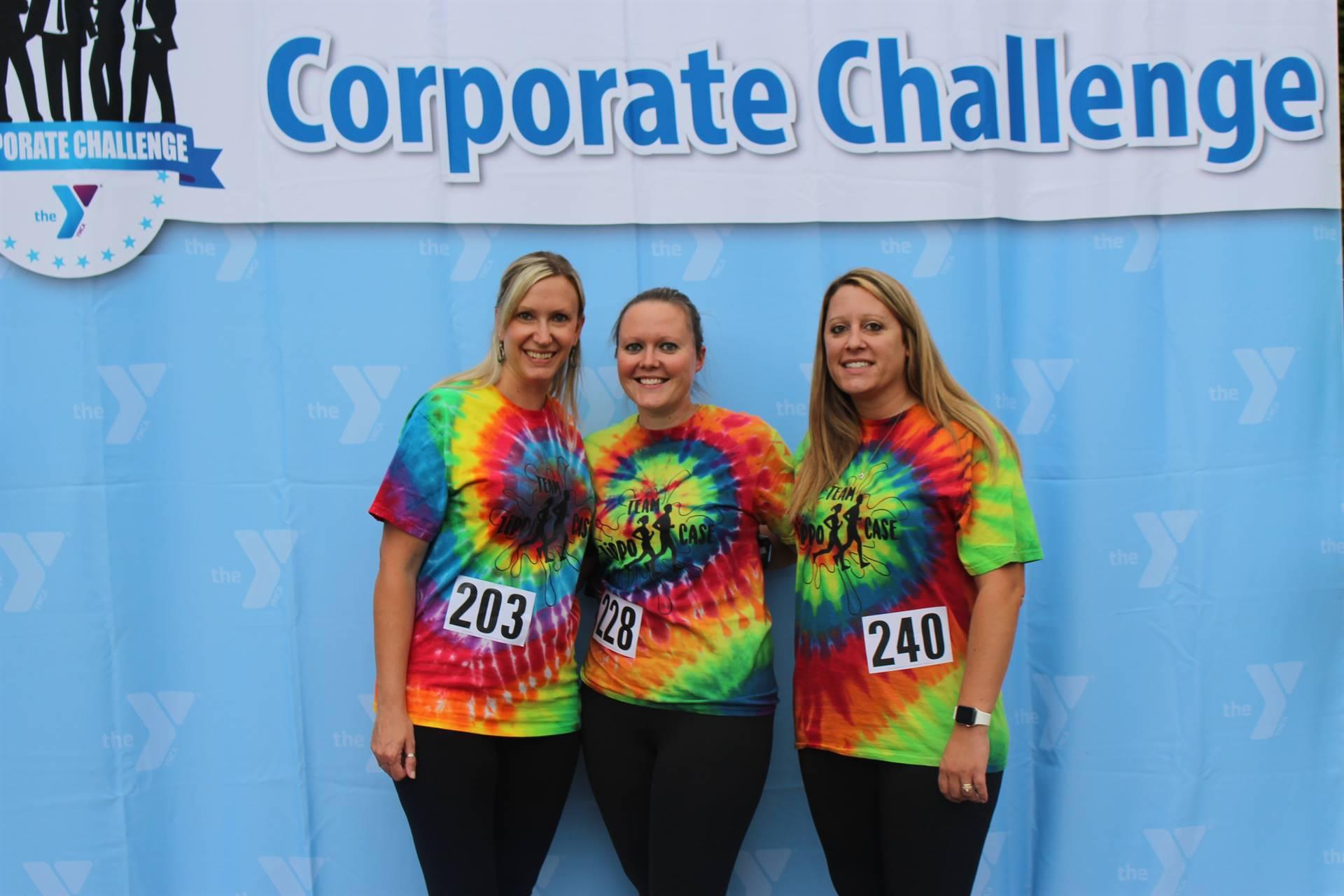 Three women in front of corporate challenge banner