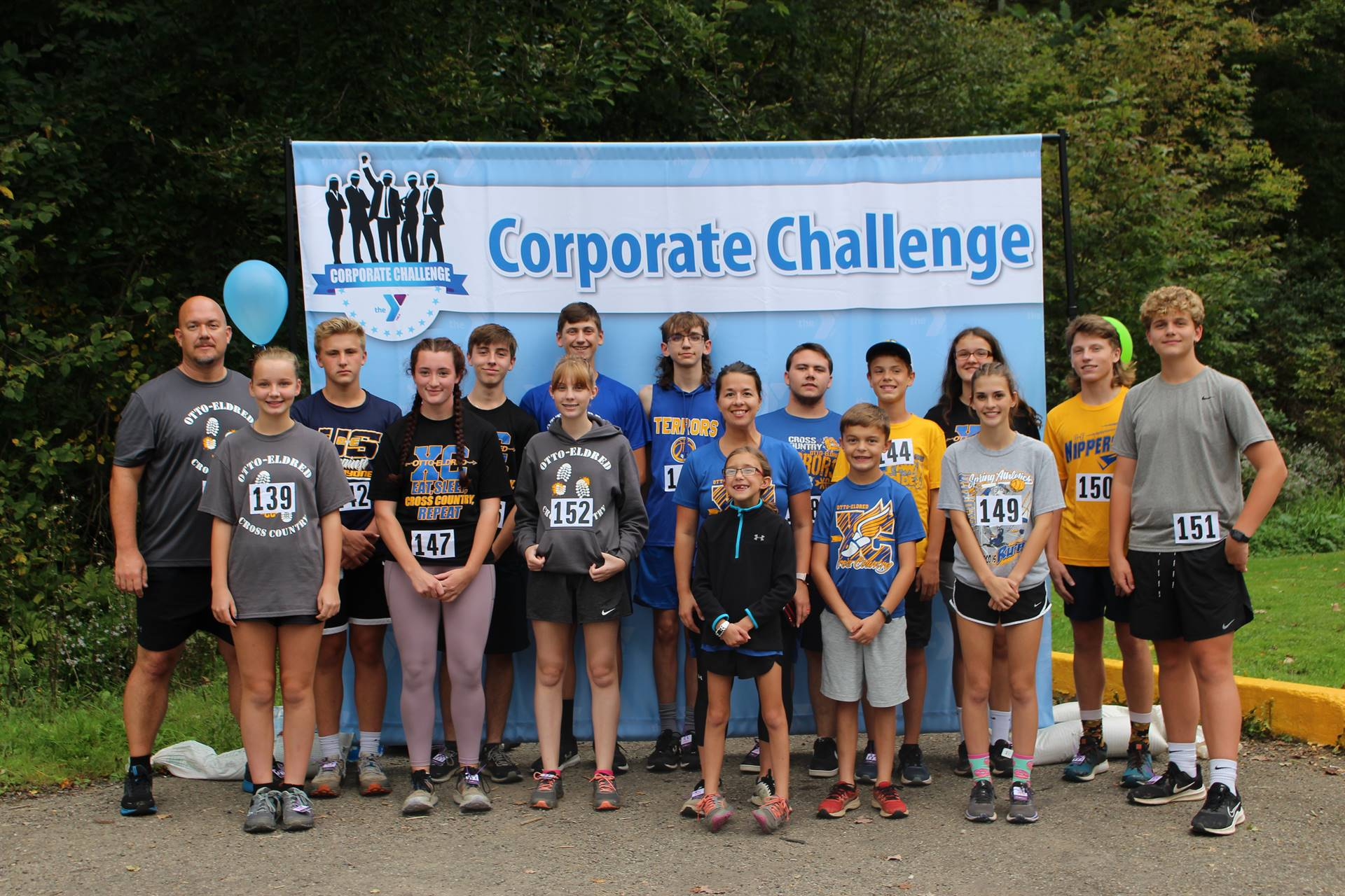 group of employees standing in front of corporate challenge banner