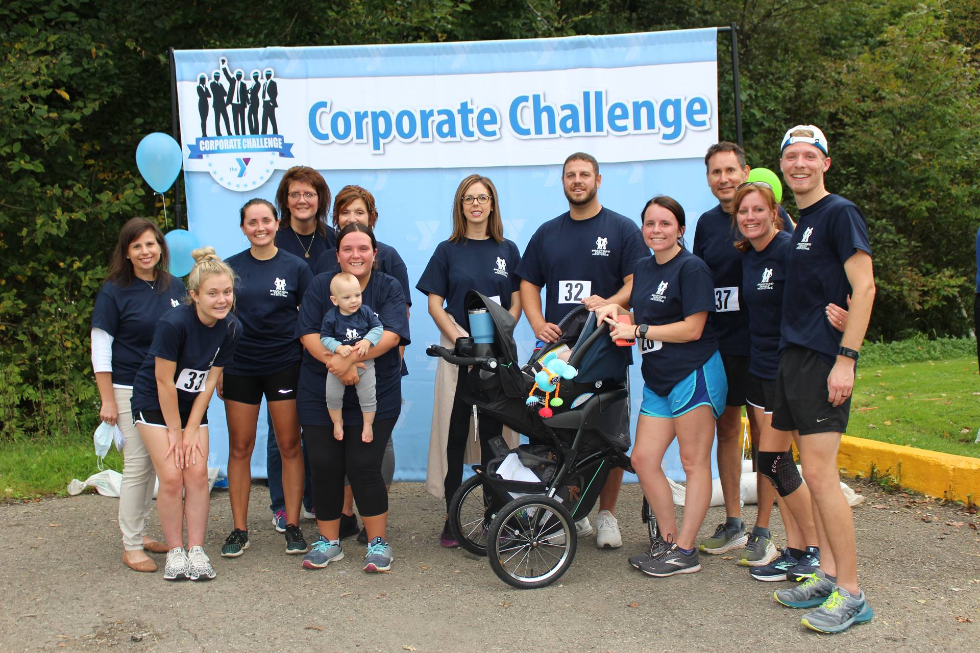 group posing in front of corporate challenge banner