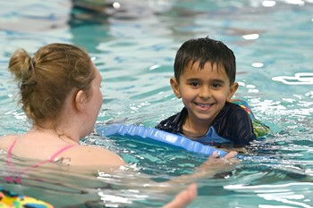 Young boy in swimming pool with adult instructor